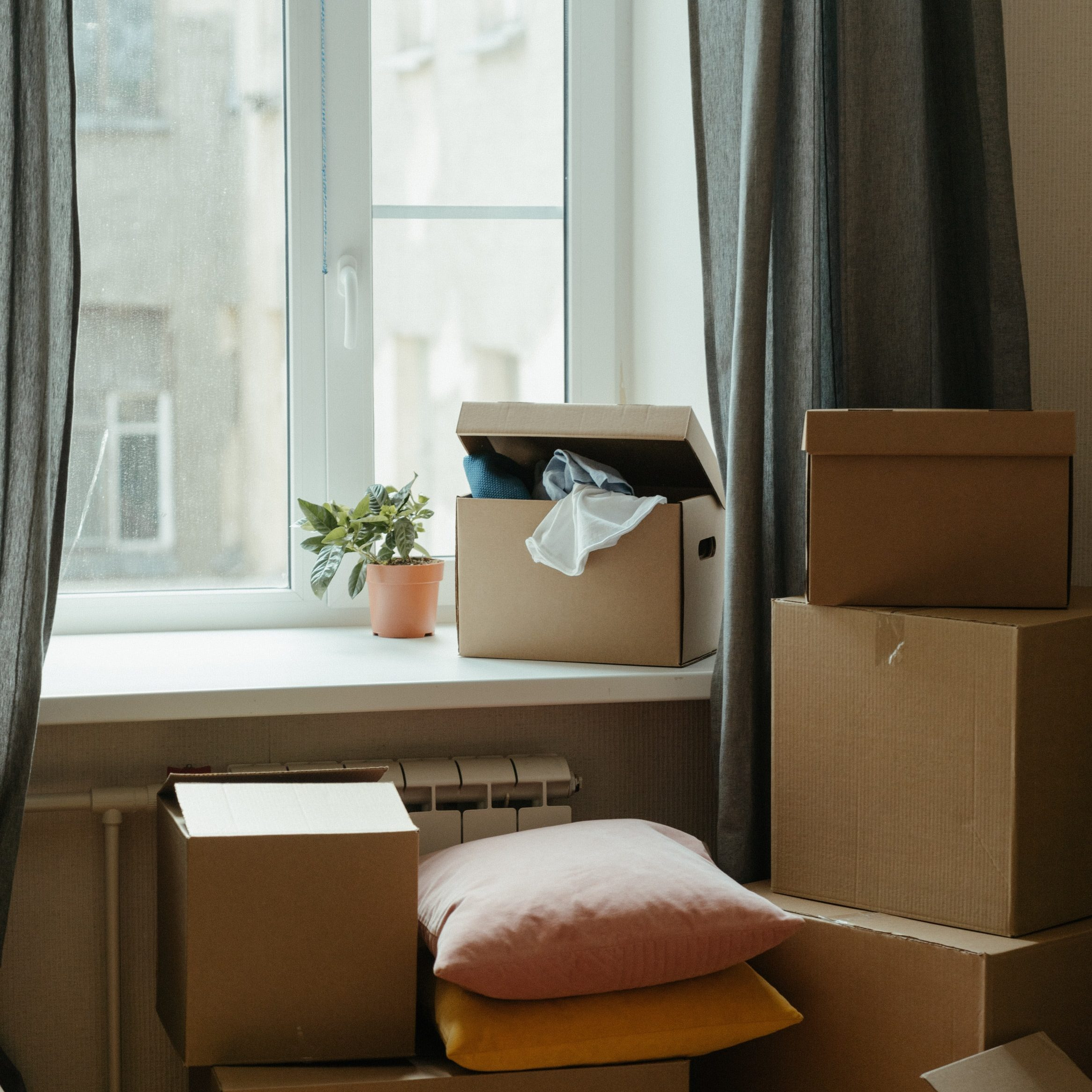 Packing boxes stacked next to a window
