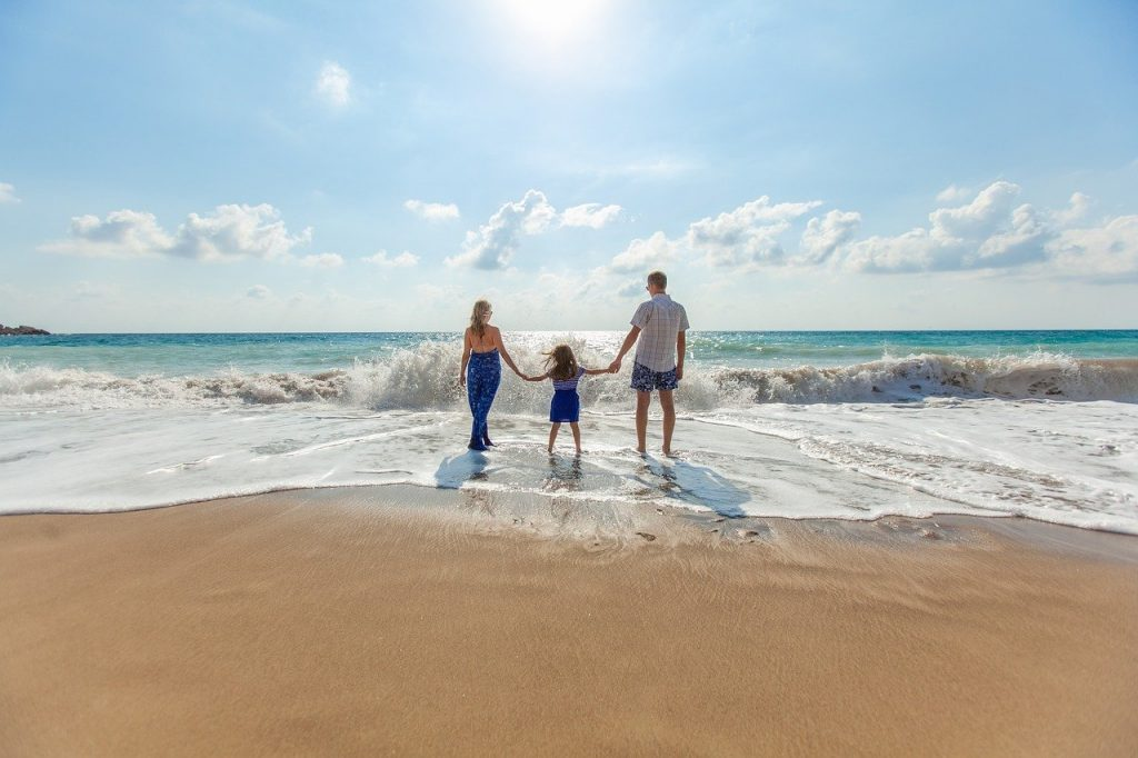 family holding hands on a beach